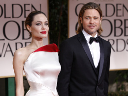 Actors Angelina Jolie and Brad Pitt pose for photographers as they arrive at the 69th annual Golden Globe Awards in Beverly Hills